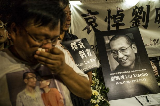 Hong Kong citizens mouth the death of Liu Xiaobo outside the Liaison Office Of The Central People's Government In The Hong Kong Special Administrative Region on Thursday. (New York Times photo)