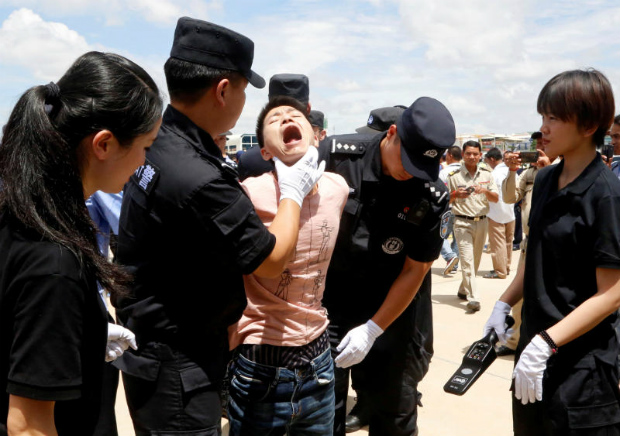 Chinese officials check the body of a suspect of telecom fraud before being deported to China, at the International Airport of Phnom Penh, Cambodia July 6, 2017. (Reuters photo)