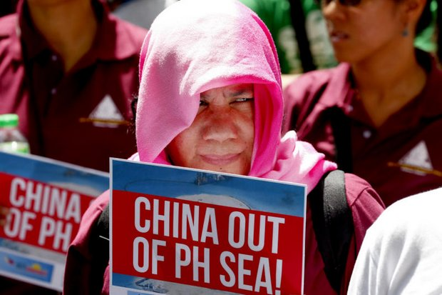 Protesters hold placards during a rally last month at the Chinese consulate in Metro Manila to protest China's artificial island-building at disputed islands, reefs and shoals off the Philippines. (AP file photo)
