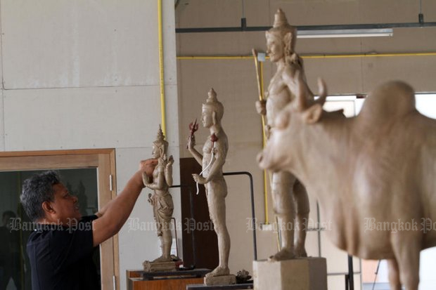 A Fine Arts Department specialist prepares figures that will be seen at the royal funeral in late October. (Bangkok Post file photo)