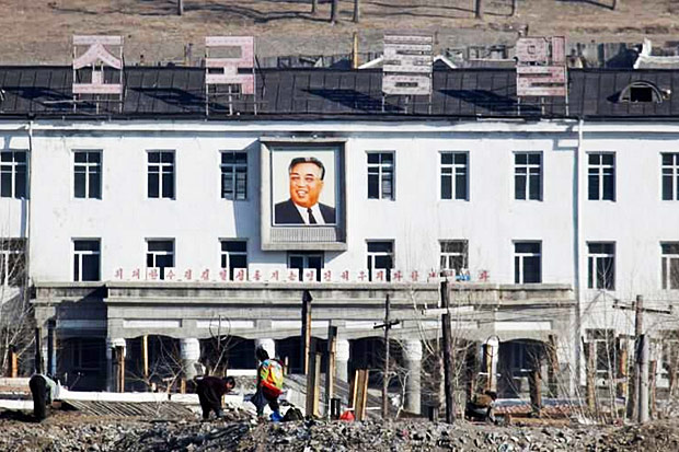 Local residents rummage through rubble near a building bearing a portrait of Kim Il-sung, the founding leader of North Korea and grandfather of the country's current leader. (Reuters photo)