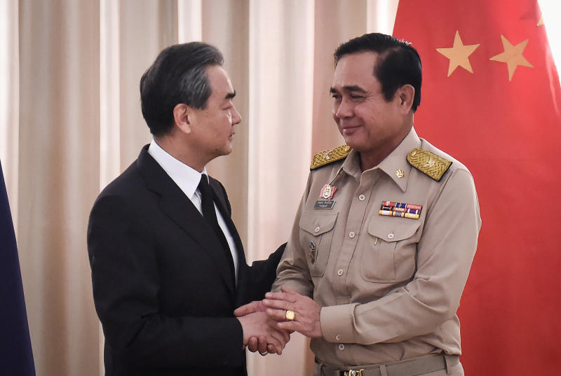 Chinese Foreign Minister Wang Yi shakes hands with Prime Minister Prayuth Chan-o-cha at Government House on Monday. (Reuters photo)