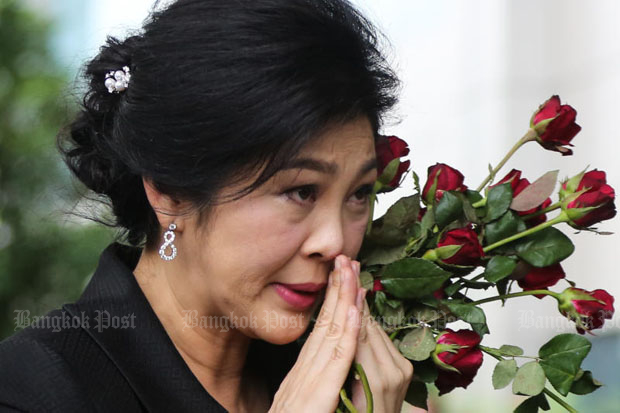 Former prime minister Yingluck Shinawatra reacts to her supporters in front of the Supreme Court's Criminal Division for Holders of Political Positions in Bangkok as she arrives to attend the last witness hearing in her rice scheme trial last Friday. (Photo by Seksan Rojjanametakun)