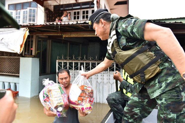 The armed forces began all-out efforts on the weekend to get relief and aid to flood-stricken areas. Above, army officers provide aid packets to stranded Sakon Nakhon residents. (Photo Twitter/@wassanananuam)