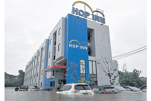 Waterlogged vehicles sit in front of Hop Inn hotel in Sakon Nakhon last week.
