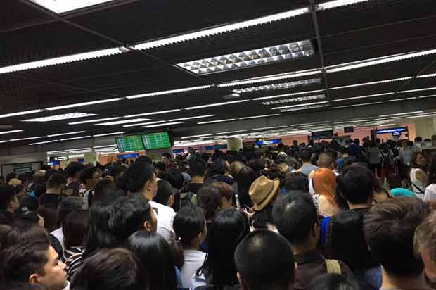 Foreign visitors queue for passport control at Don Mueang airport during a four-hour wait that stretched into Saturday morning. (Photo from the Facebook page of Piyabutr Saengkanokkul)