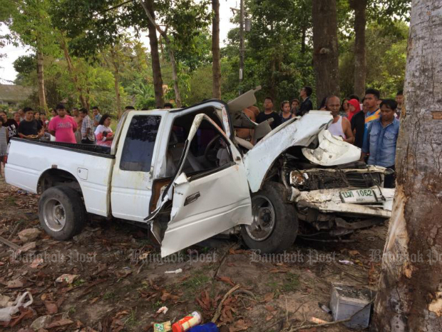 Nearby residents gather to look at a pickup truck that crashed into a roadside tree in Nakhon Si Thammarat province during Songkran on April 13, 2017, killing one woman on board and seriously injuring the two others. (Bangkok Post photo)