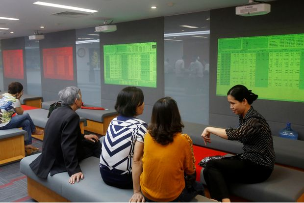 Investors talk in front of stock market screens at a securities company in Hanoi on April 20, 2016. (Reuters photo)