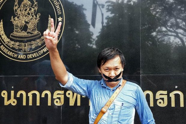 In this picture taken three days after the May 22, 2014, coup, journalist Pravit Rojanaphruk flashes a V-sign outside a Bangkok military office. (File photo)