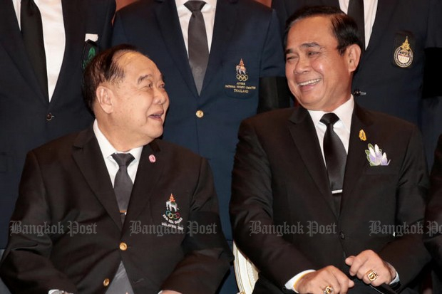Prime Minister Prayut Chan-o-cha and his deputy, Prawit Wongsuwon share a light moment while talking Wednesday with Thai athletes bound for the 19th SEA Games. The two agree that the 100% ban on political activities will remain in place indefinitely. (Photo by Chanat Katanyu)