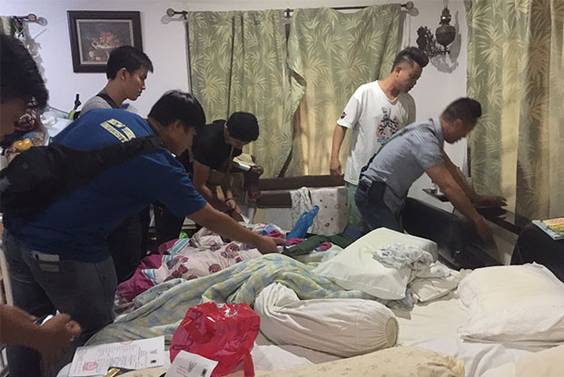 Police search the bedroom of Rachin Tantranont, 38, a Chiang Mai municipal councillor, during a raid on his house on Saturday morning. (Photo by Cheewin Sattha)
