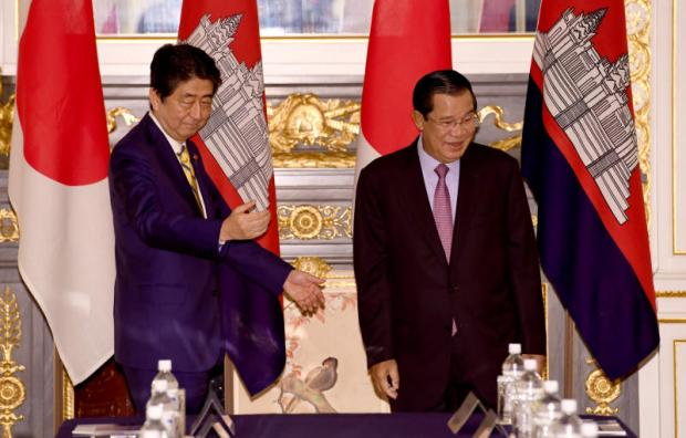 Cambodian Prime Minister Hun Sen (right) is shown his way by his Japanese counterpart Shinzo Abe prior to their meeting at the state guesthouse in Tokyo on Aug 7. (Reuters photo)