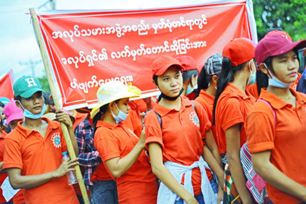 About 2,000 factory workers march for a higher basic wage in Yangon on Sunday. (Myanmar Times photo)