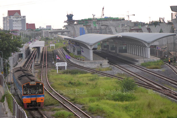 A train is passing a station. The State Railway of Thailand (SRT) will buy 100 more new diesel-electric locomotives. (Bangkok Post file photo)