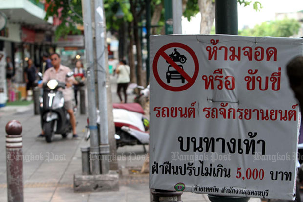 A man is seen riding his motorcycle on a footpath near a sign prohibiting  motorcycles or vehicles parking on or riding on the sidewalk. It warns violators face a fine of up to 5,000 baht. (Photo by Apichart Jinakul)