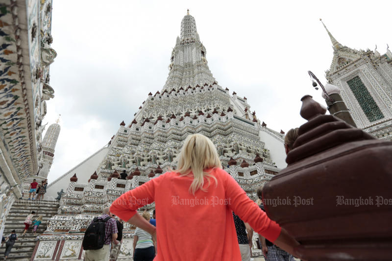 A tourist looks at the Temple of Dawn's stupa on Wednesday. (Photo by Patipat Janthong)
