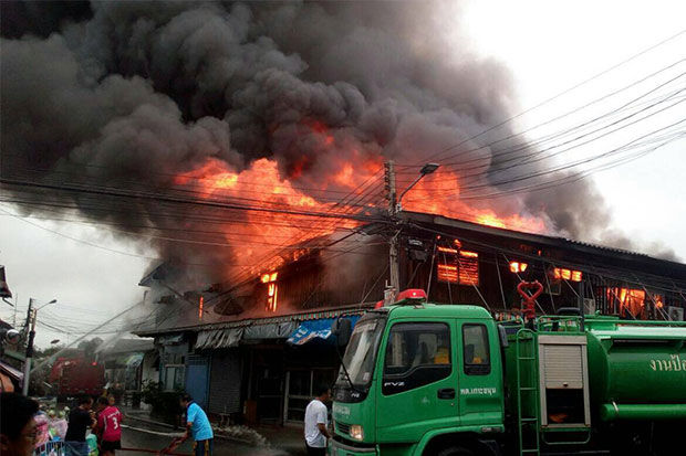 A fire rages through wooden shophouses at a market in Chachoengsao's Phanom Sarakham on Saturday morning, destroying seven units of the shophouses built in a row. (Photo by Sonthanaporn Inchan)