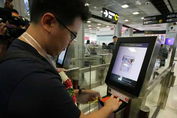 A Singaporean passenger uses an automatic gate to check himself through immigration clearance at Suvarnabhumi Airport on Saturday. (Photo by Apichit Jinakul)