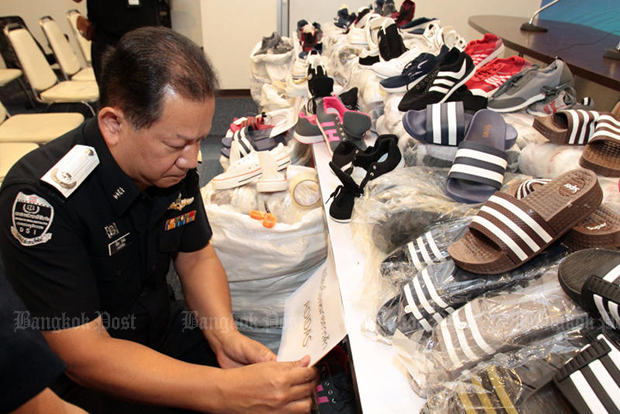 A DSI officer with seized, falsely branded footwear at a media briefing on Monday.  (Photo by Tawatchai Kemgumnerd)