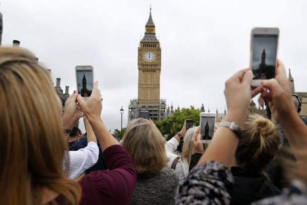 A crowd records the last bell at Elizabeth Tower in London on Monday, as Big Ben bongs for noon and then falls silent until 2021. (AP photo)