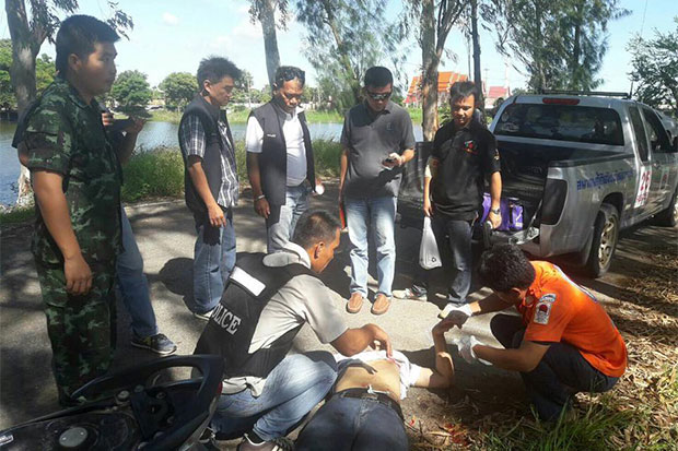A 26-year-old man who allegedly stole a pistol from a shooting range and shot dead his father in Lop Buri on Monday, lies on the ground, shot and wounded during an exchange of gunfire with police in neighbouring Sing Buri district on Tuesday morning. (Photo taken from Siang Thong Thin (local voice) Facebook page)