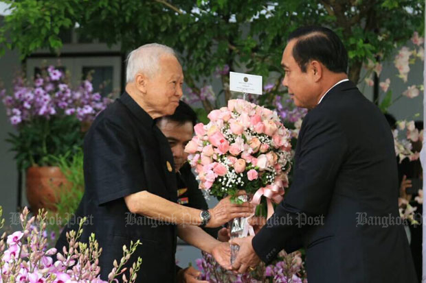 Privy Council president Prem Tinsulanonda, left, receives a bouquet from Prime Minister Prayut Chan-o-cha at his residence in Bangkok on Thursday. (Photo by Wassana Nanuam)