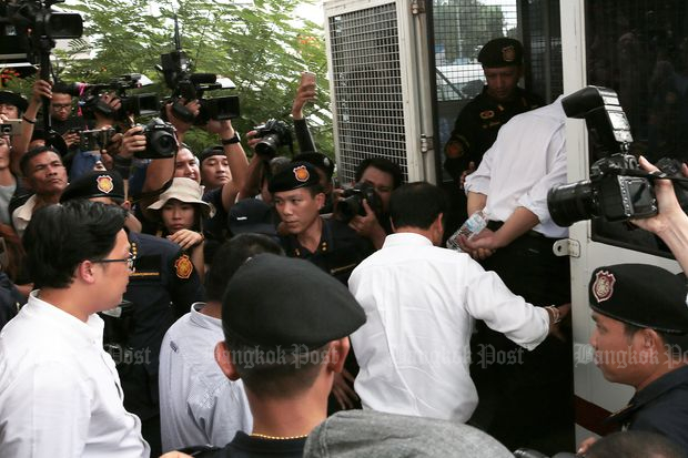 The defendants in the rice sales case including former commerce minister Boonsong Teriyapirom get on a bus to be brought to Bangkok Remand Prison after the ruling on Friday. (Photo by Chanat Katanyu)