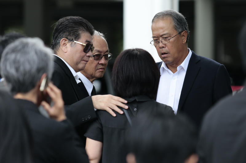 Pheu Thai Party members talk after they were informed that former prime minister Yingluck Shinawatra failed to appear for the ruling on Friday. (Photo by Patipat Janthong)
