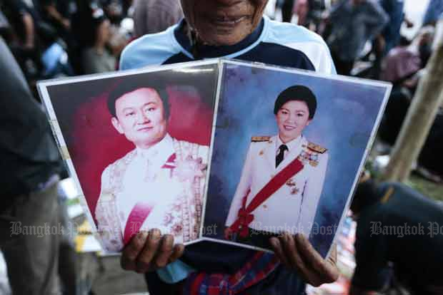A supporter holds images of former prime minister Yingluck Shinawatra and her brother Thaksin on Aug 1, the day when Ms Yingluck made the closing statement in her trial. (Bangkok Post file photo)
