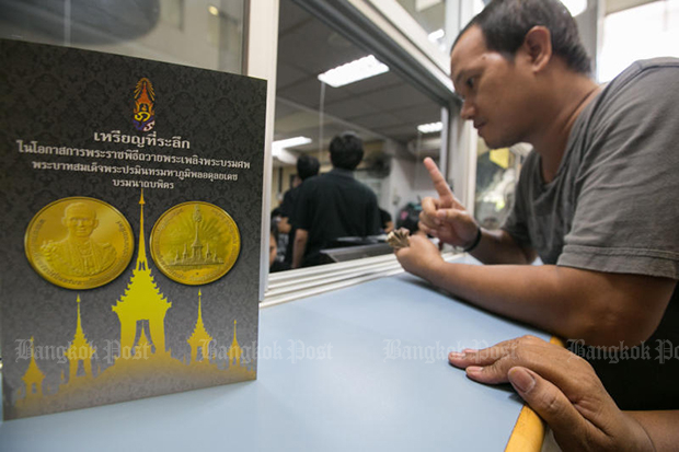 A man places an order for a commemorative cremation coin last Tuesday. (Bangkok Post file photo)