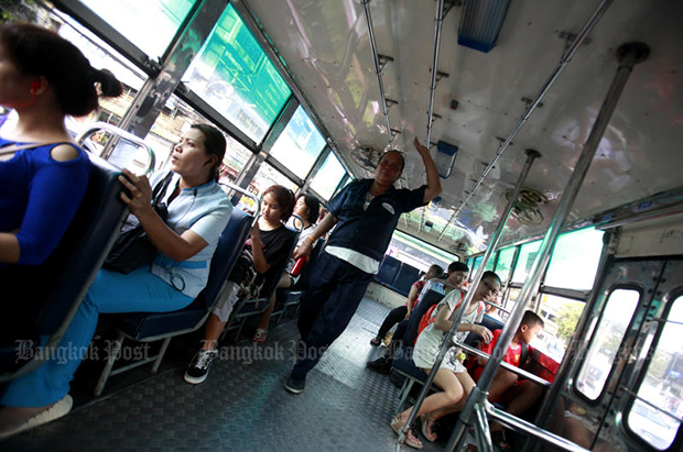 A bus conductor walks inside her bus in Bangkok. As many as 2,000 conductors will be offered a one-million-baht early retirement package. (Bangkok Post file photo)