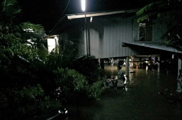 A villager in Ban Ko Ta Moi in Prachin Buri carries her belongings to safety through the floodwater surrounding her house overnight. (Photo by Manit Sanubboon)