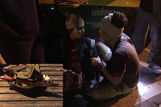 Two Chinese tourists given first aid for wounds to the head inflicted by a lone robber wielding a long-bladed knife, seen on the table, in Samut Prakan's Bang Bo district in the early hours of Thursday. (Photo by Sutthiwit Chayutworakan)