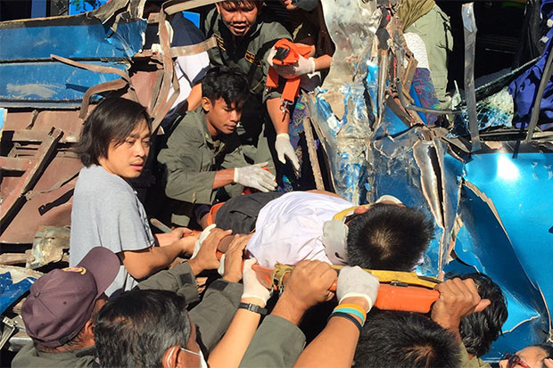 Rescue workers rush to take injured students to a hospital following a school bus-truck crash in Muang district, Chai Nat on Friday morning. (Photo by Chudate Seehawong)