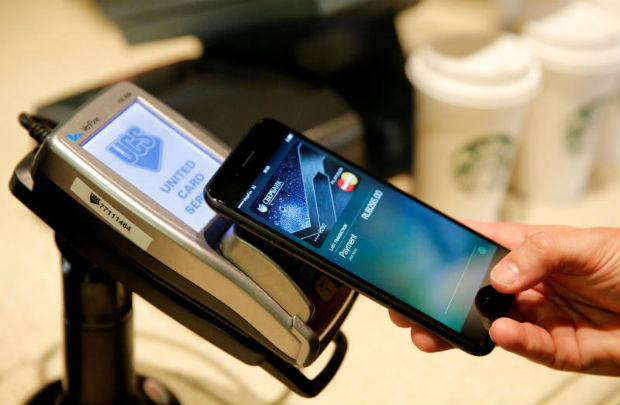 A man uses an iPhone 7 smartphone to demonstrate the mobile payment service Apple Pay at a cafe in Moscow, Russia, October 3, 2016. (Reuters file photo)