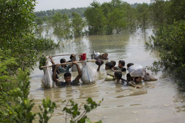 A Rohingya family reaches the Bangladesh border after crossing a creek of the Naf river on the border with Myanmmar, in Cox's Bazar's Teknaf area, on Monday. (AP Photo)