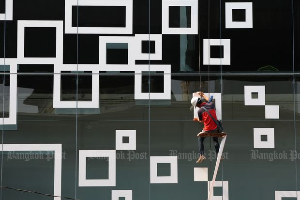 A worker cleans the exterior of Siam Discovery shopping mall in Bangkok. (Bangkok Post file photo)