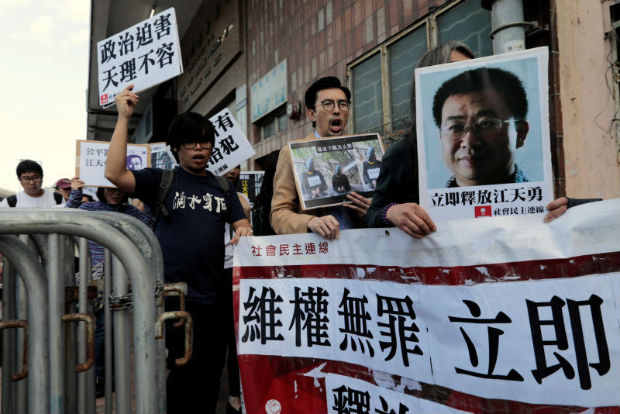 Pro-democracy demonstrators hold up portraits of Chinese disbarred lawyer Jiang Tianyong, demanding his release, during a demonstration outside the Chinese liaison office in Hong Kong, China December 23, 2016. (Reuters file photo)