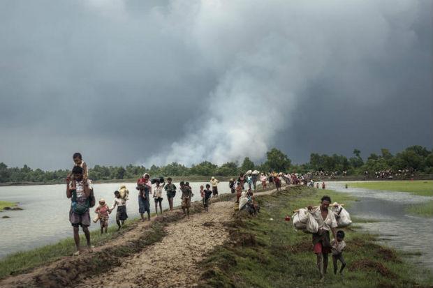 Villages burn in the distance as Rohingya refugees walk near the Naf River separating Myanmar and Bangladesh, near Palong Khali, Bangladesh, Sept 4, 2017. (Adam Dean/The New York Times)