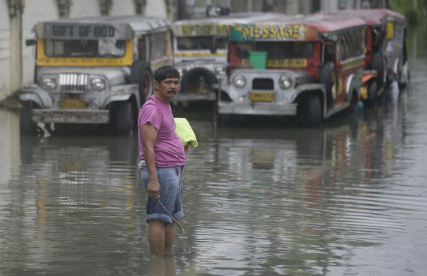 A man stands in front of passenger jeepneys along a flooded street due to heavy rains from Tropical Depression Maring on Tuesday, in Marikina city, Manila, Philippines. Maring has dumped heavy rains in the Philippines, flooding metropolitan Manila and nearby provinces and causing a landslide in some areas. (AP Photo)