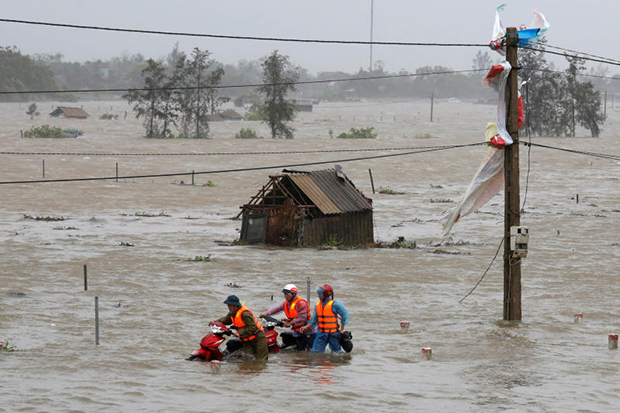 People recover motorbikes from a flooded fields while the Doksuri storm hits in Ha Tinh province in Vietnam on Friday. (Reuters photo)
