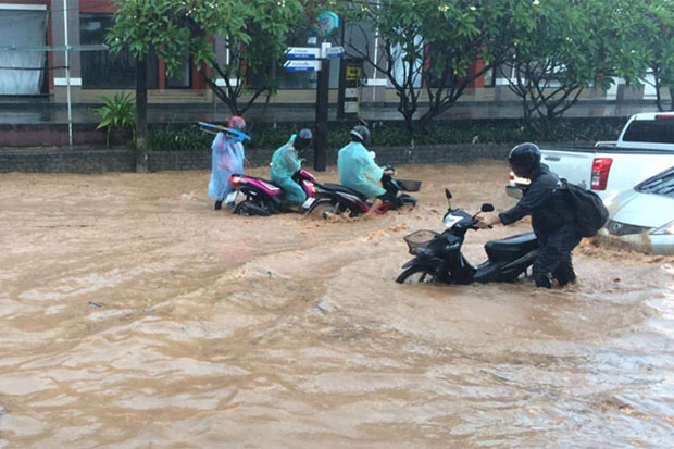 Motorcyclists wade through floodwaters in Patong area of Phuket on Friday after heavy rain. (Photo by Preecha Ritthirtree)