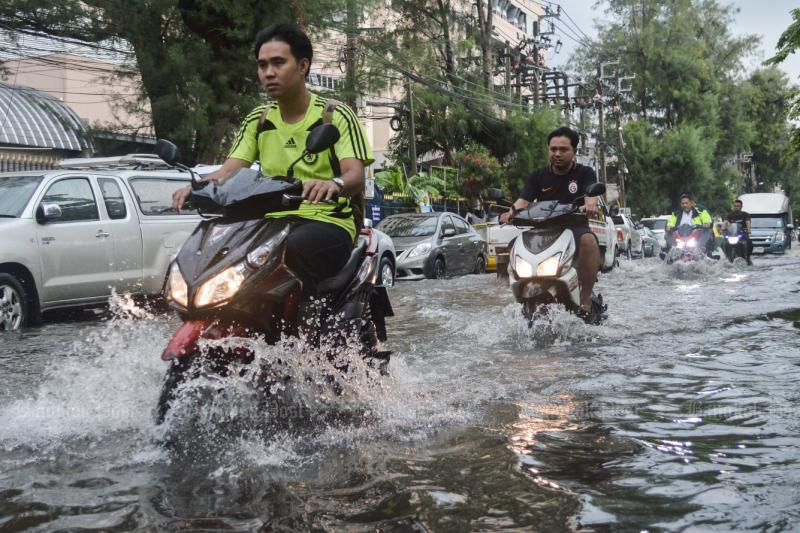 Motorcyclists travel along flooded Mitmaitree Road in Din Daeng district after heavy rain pounded most of Bangkok on Wednesday. (Photo by Worrapon Phayakum)