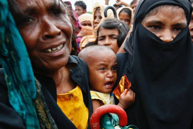 A Rohingya refugee baby cries as his mother jostles for aid in Cox's Bazar, Bangladesh on Wednesday. (Reuters photo)