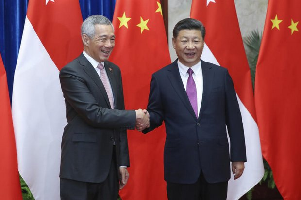 Singapore Prime Minister Lee Hsien Loong, left, shakes hands with China's President Xi Jinping in Beijing, during a meeting to patch up relations following months of tensions over China's claims in the South China Sea. (AP photo)