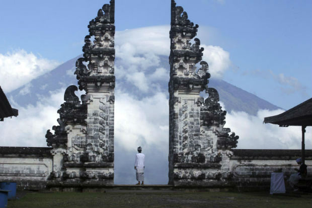 A Balinese man watches Mount Agung volcano almost covered with clouds as he stands at a temple in Karangasem, Bali, Indonesia, on Tuesday.,(AP Photo)