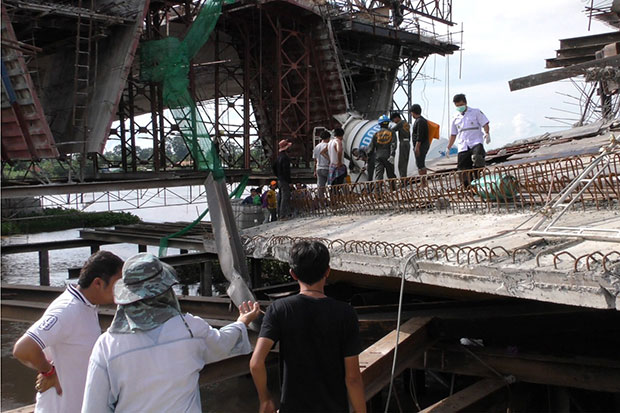 Authorities inspect the site of a collapsed bridge across the Chao Phraya River in Chai Nat's Muang district on Saturday. (Photo by Chudate Seehawong)