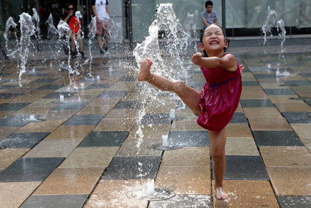 A girl plays in a water fountain to cool off on a hot day in Beijing on July 12, 2017. About 70% of Beijing's water is provided by the South-to-North Water Diversion project. (Reuters photo)