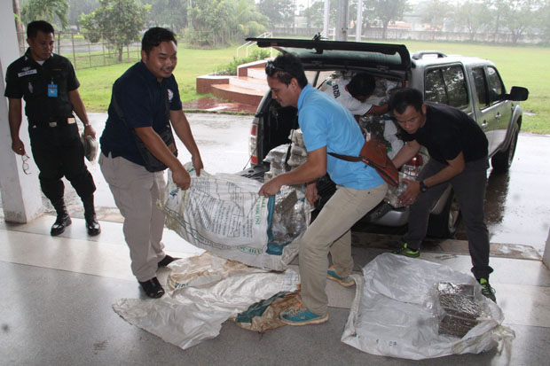 Border patrol police unload packs of marijuana from a Chevrolet pickup truck at the 24th Border Patrol Police unit in Muang district, Udon Thani, on Wednesday. (Photo by Yuttapong Kumnodnae)