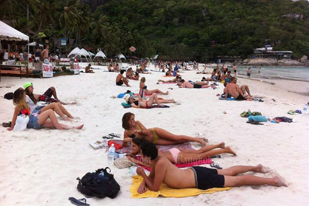 Tourists sunbathe on Rin beach on Koh Phangan. Authorities in Koh Phangan district will crack down on illegally-run guesthouses from Oct 16. (Bangkok Post file photo)